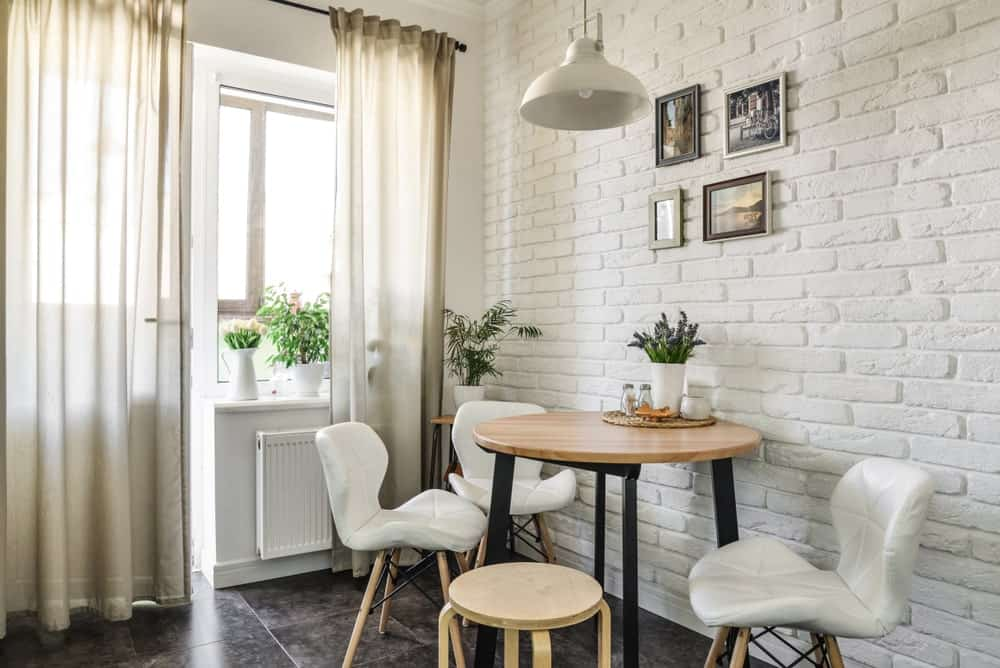 A white brick accent wall mounted with a photo gallery creates texture in this dining room with tiled flooring and glazed windows covered in sheer curtains. It includes a dome pendant light and a black metal dining table surrounded by stylish chairs.