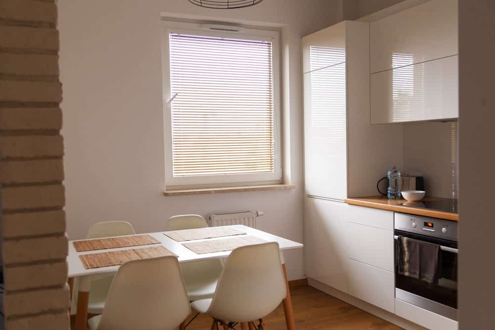 The sleek dining area offers modern chairs and a dining table topped with wicker placemats that complement the hardwood flooring. It has a white framed window covered in blinds.
