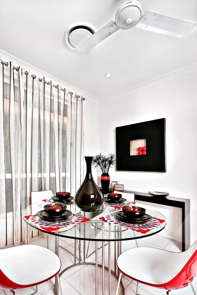 A modern black wall art hangs above the sleek buffet table topped with a vase and decorative bowl. This dining room boasts a glass top dining table and contemporary chairs over white tiled flooring.