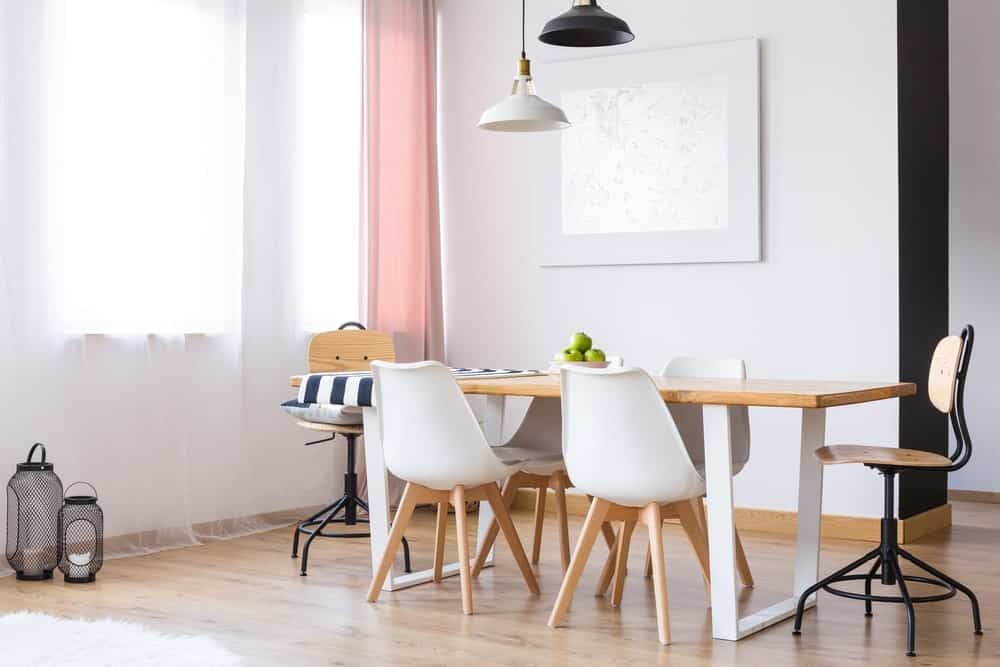 Mismatched chairs surround a rectangular dining table topped with a nautical runner. It is illuminated by a black and white dome pendants along with natural light that flows in through the large windows covered in sheer and pink drapes.