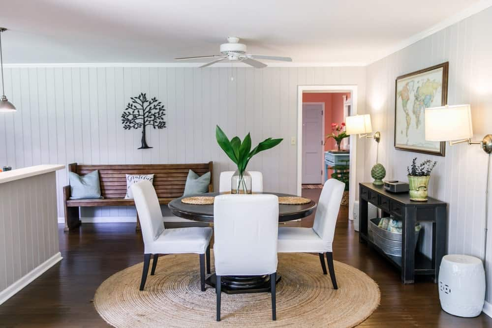 This dining area is decorated with a tree and framed wall arts mounted on the beadboard walls. It has a dark wood dining table and upholstered chairs that sit on a round jute rug over the hardwood flooring.