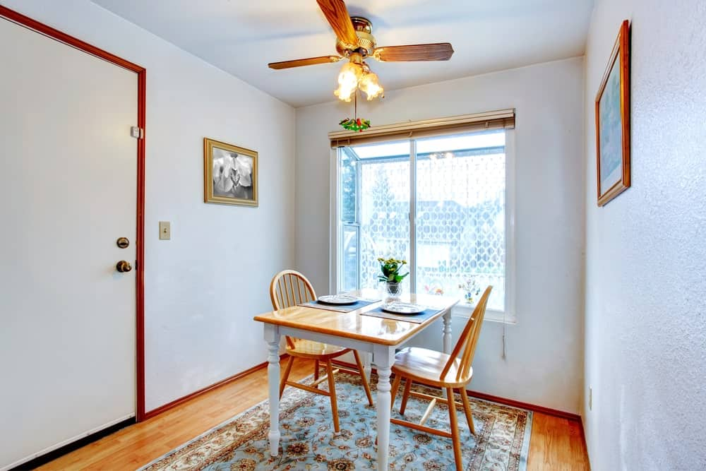 A traditional ceiling fan hangs over the wooden dining table and round back chairs that sit on a blue floral rug over the rich hardwood flooring. This room showcases a glazed window and framed artworks mounted on the white walls.