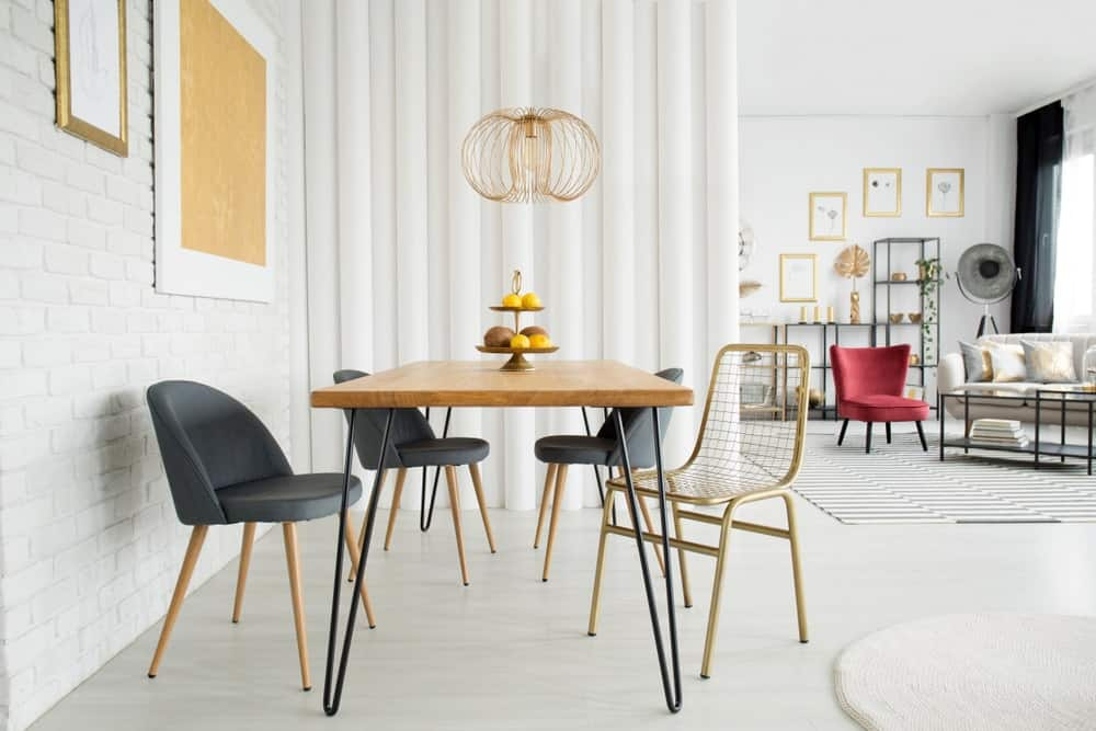 An open dining area with a stylish pendant light that hung over the wooden dining table accompanied by brass perforated and black modern chairs. It is decorated with framed artworks mounted on the white brick accent wall.