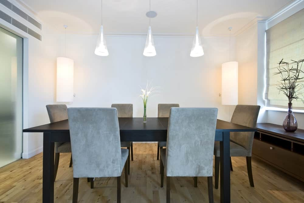 Cone pendant lights along with cylindrical wall sconces illuminate this dining room featuring a black dining table and gray velvet chairs across the wooden console table.