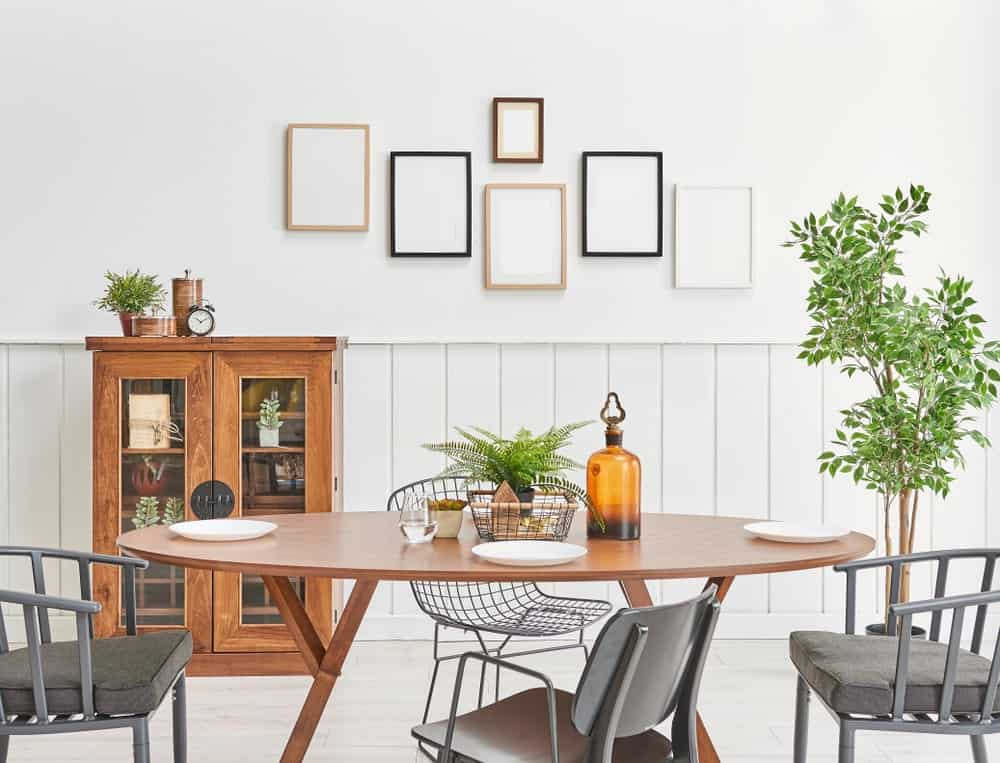 A closeup look at this dining room with an oval dining table and mismatched chairs over the light hardwood flooring. It includes a display cabinet and gallery frames mounted above the beadboard wall.