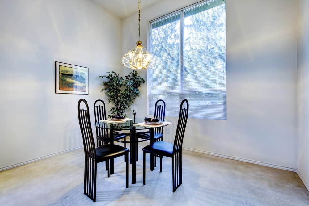 Fresh dining room features black leather chairs and a round dining table lighted by a brass chandelier. There's a potted plant in the corner next to the picture window that's covered in roller blinds.