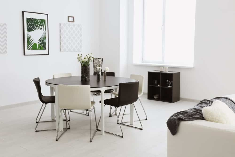 White dining room with a small shelving unit and round dining table surrounded by alternating white and black chairs. It has light hardwood flooring and a glazed window inviting natural light in.