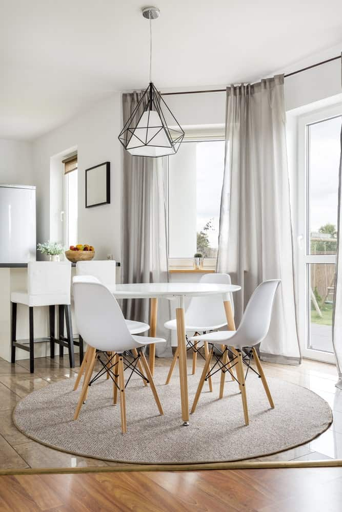 A round area rug lays on the wide plank flooring in this dining area with modern white chairs and a round dining table illuminated by a geometric pendant light.