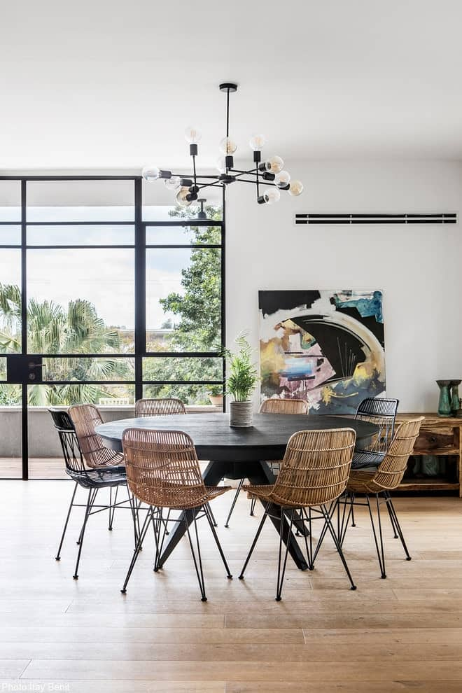 Cozy dining room with light hardwood flooring and full height windows inviting an ample of natural light in. It includes wicker chairs and a round dining table illuminated by a contemporary chandelier.