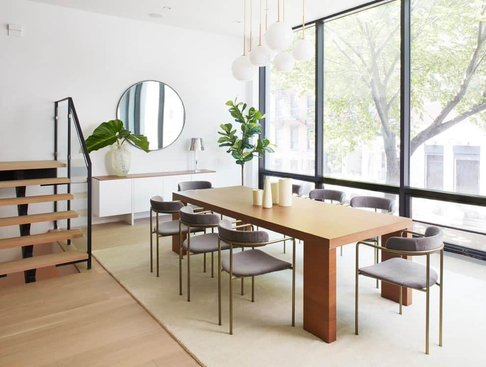 Airy dining room designed with globe pendant lights and a round mirror mounted above the white console table. It includes a smooth wooden dining table surrounded by sleek chairs and a fiddle leaf fig plant that creates a tropical feel in the room.