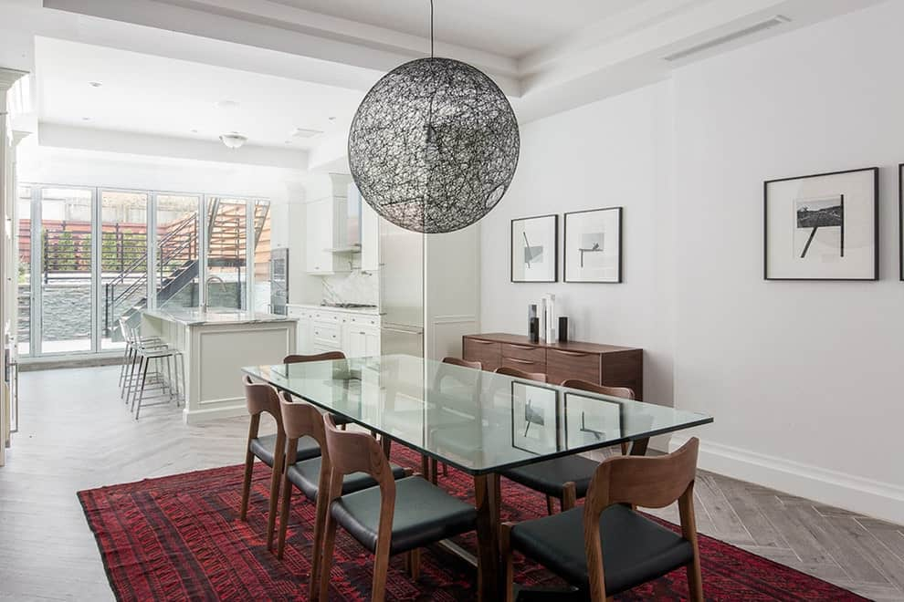 Contemporary dining room with a tray ceiling and herringbone wood flooring topped by a red area rug. It is decorated with a large spherical pendant along with minimalist wall arts that are mounted on the white wall.