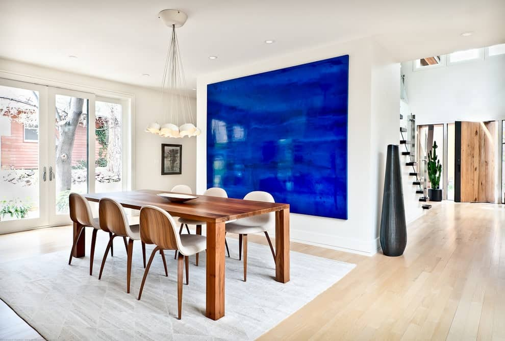 A vibrant blue artwork brings a pop of color in this white dining room offering a wooden dining set on a gray area rug over the light hardwood flooring. It is illuminated by a clustered chandelier along with recessed ceiling lights.