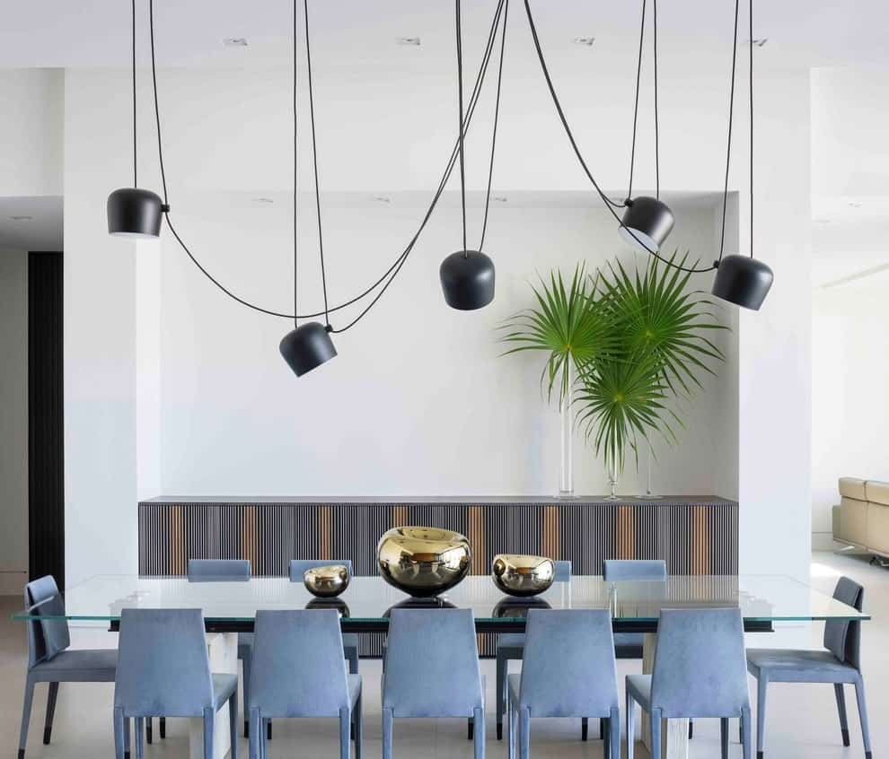 A built-in buffet table topped with sleek glass vases stands out against the walls in this dining room with blue velvet chairs and a glass top dining table illuminated by industrial pendant lights.