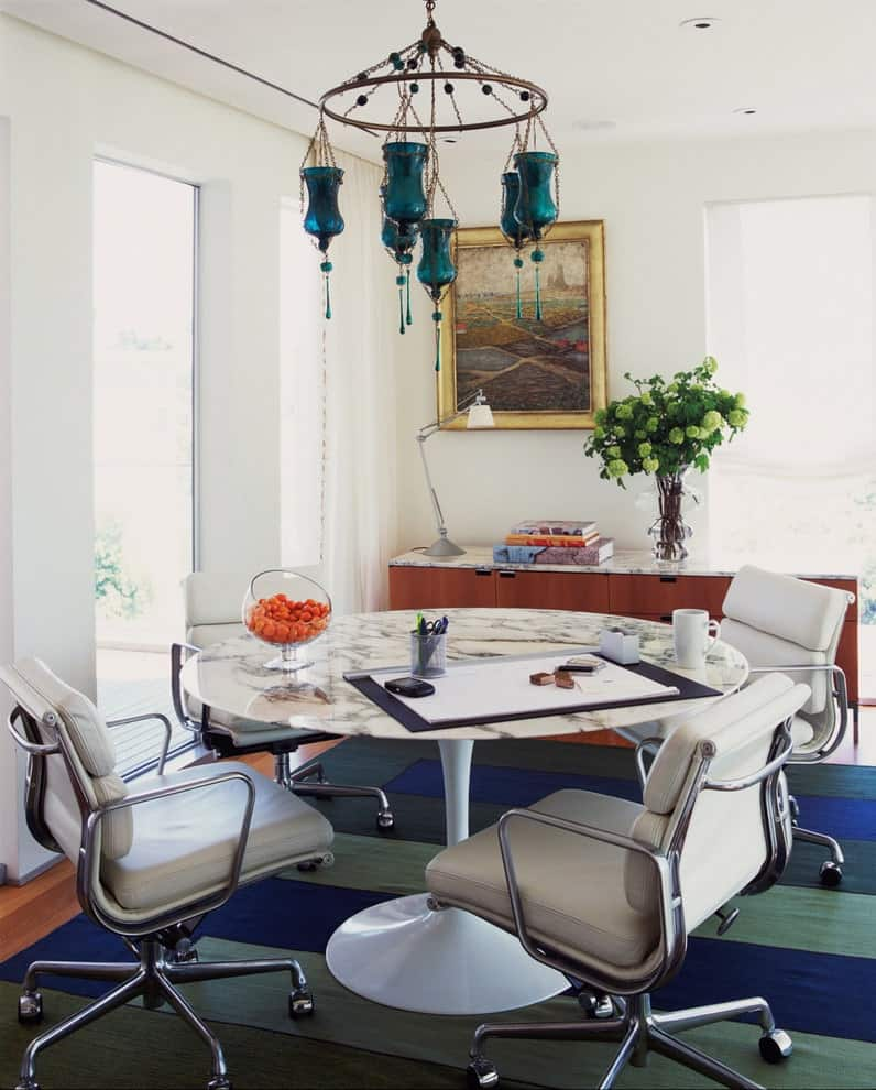 Brass framed wall art hangs above the wooden buffet table that's topped with a marble counter matching with the round dining table over a multi-colored area rug. It is accompanied by a gorgeous chandelier along with beige leather swivel chairs.