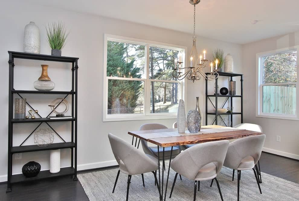 Metal shelving units filled with various decors flank a white framed window that's fixed across the cozy dining set illuminated by a candle chandelier. It sits on a gray area rug over the dark hardwood flooring.