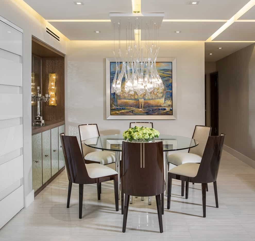 This dining room is decorated with a gorgeous painting and a stylish glass chandelier that hung over the round dining table surrounded by cushioned chairs. It has tiled flooring and a suspended ceiling mounted with recessed lights.
