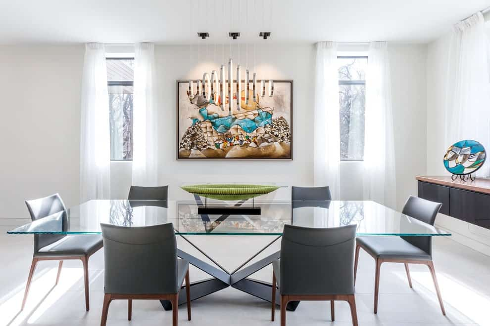 Glazed windows covered in sheer curtains flank a gorgeous wall art that hung above the green console table. It is accompanied by a floating buffet table and modern dining set lighted by round pendants that are arranged in a diamond pattern.