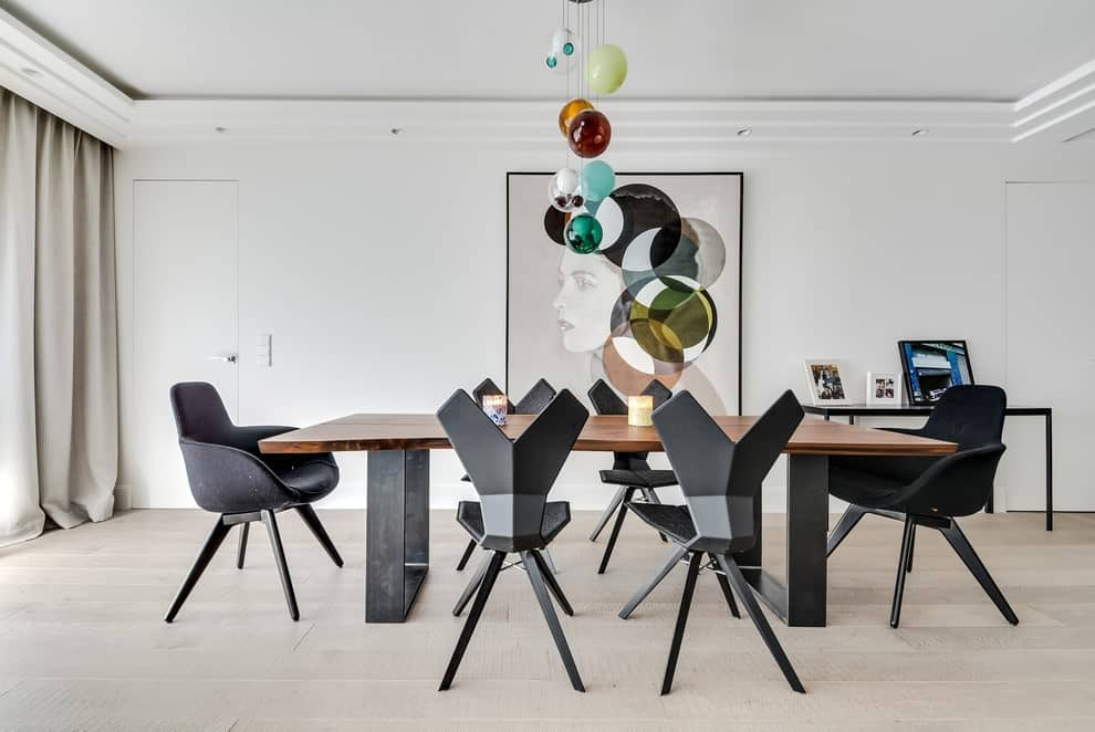 Stylish black dining set adds a striking contrast to the white walls mounted with a gorgeous portrait. This dining room showcases multi-colored globe pendants and a metal console table topped with framed photos.