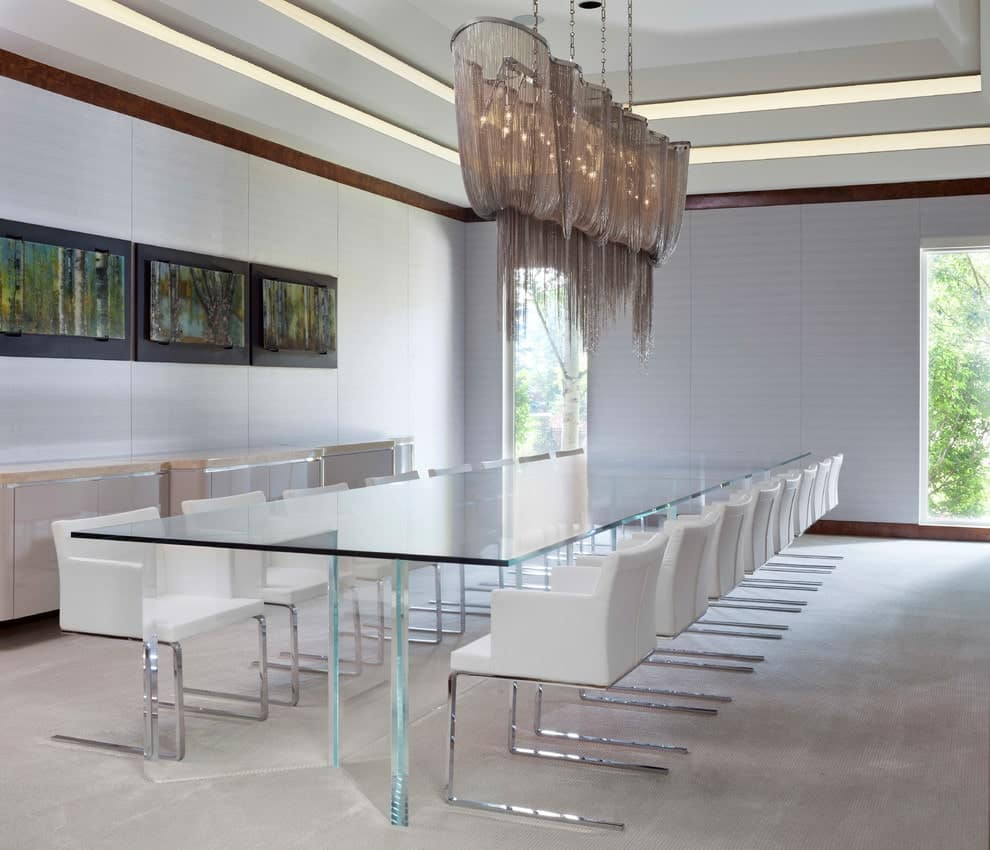 The fabulous dining room features a beige console table with silver trims under black framed paintings along with a glass dining table flanked by sleek white chairs. It is illuminated by a boho chandelier that hung from the tray ceiling.