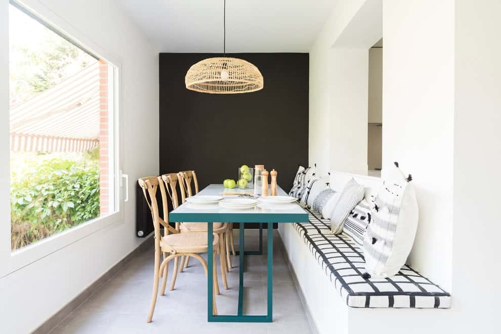 The contemporary dining room offers a rectangular dining table flanked by wooden chairs and a built-in bench that's topped with plaid sectional cushions and black and white pillows. It is illuminated by a wicker chandelier along with natural light from the picture window.