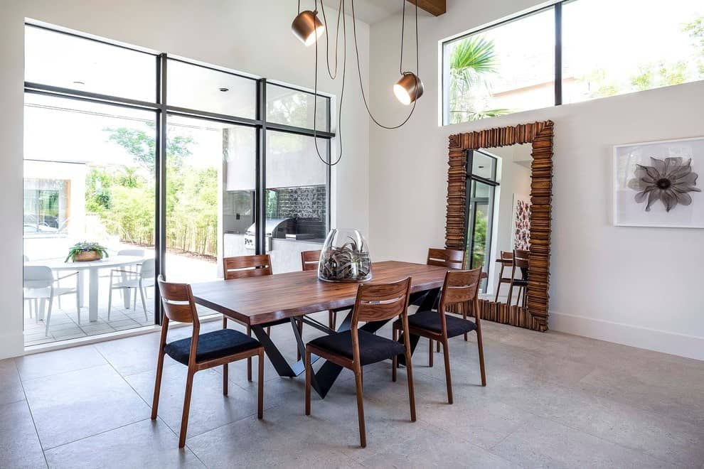 A full-length mirror complements the wooden dining set illuminated by copper pendant lights. This dining room has concrete tiled flooring and glazed windows allowing natural light in.
