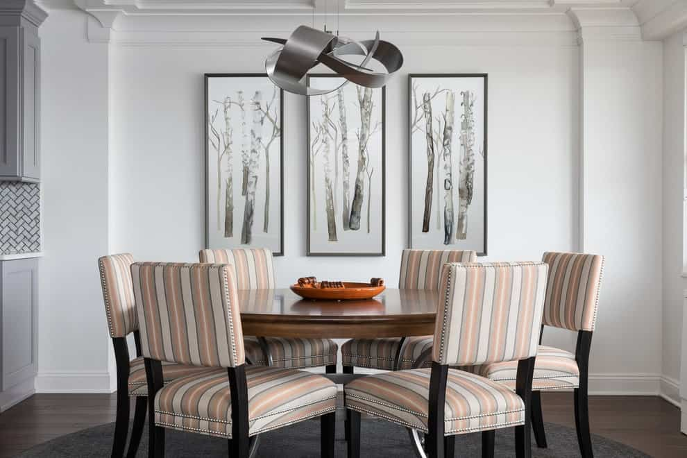 Striped cushioned chairs surround a dark wood dining table lighted by a unique chrome chandelier. This dining room is decorated with branch artworks mounted on the white wall.