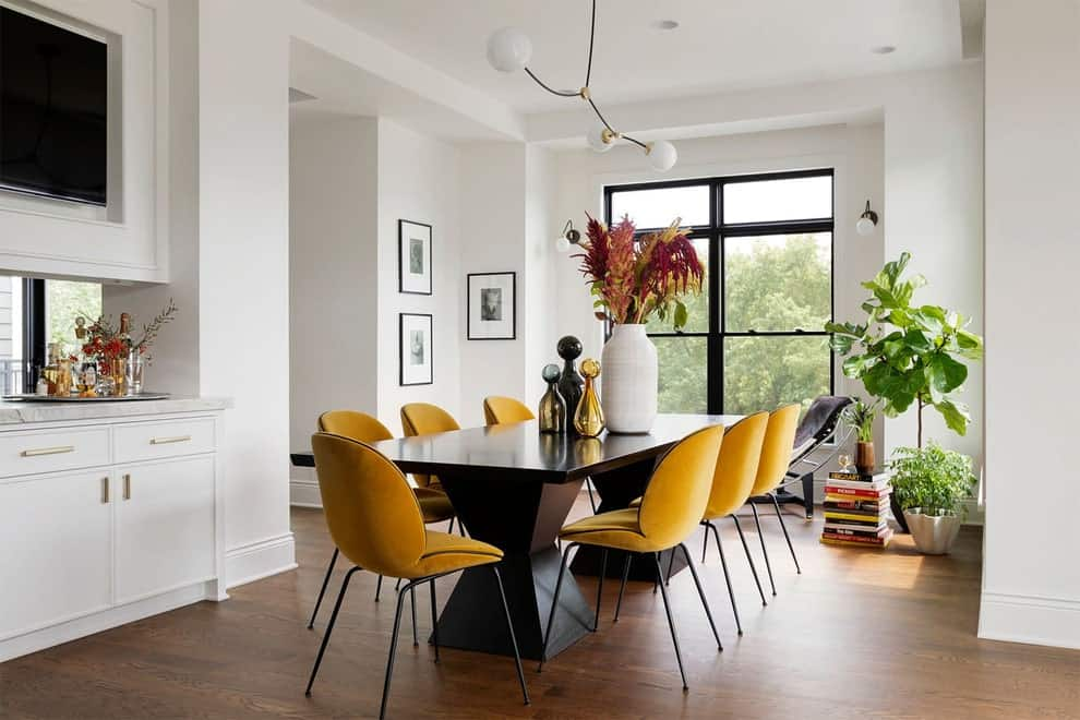 White dining room contrasted by a black dining table that's paired with yellow round back chairs. It has natural hardwood flooring and a full height window flanked by globe sconces.
