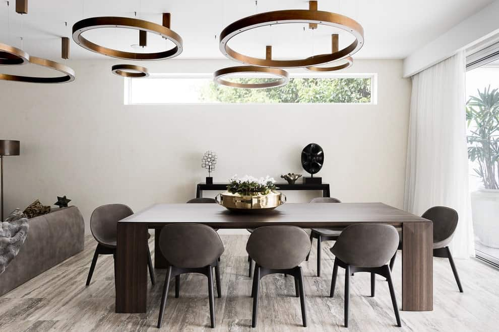 This dining room offers a dark dining set and a sleek black buffet table topped with stylish decors. It includes plenty of round pendant lights that hung from the regular white ceiling.
