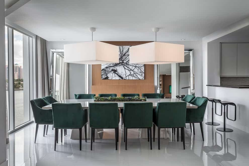 Contemporary dining room illuminated by oversized pendant lights that hang over the long dining table surrounded by green modern chairs. It is decorated with a chrome framed mirror along with a black and white painting mounted on the wood paneled wall.