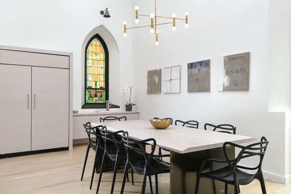 A stained glass window stands out against the white walls that are mounted with a cone sconce and gray artworks. This dining room boasts a stylish dining set that's topped with a decorative bowl complementing with the brass chandelier.