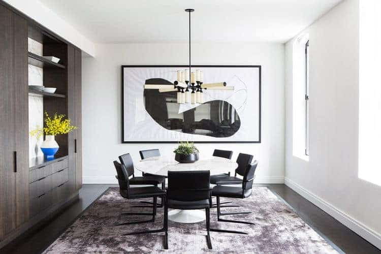 This dining room is decorated with a large black and white artwork along with a contemporary chandelier that hung over the marble dining table surrounded by sleek black chairs. There's a dark wood cabinet on the side that blends in with the hardwood flooring topped by a gray velvet rug.