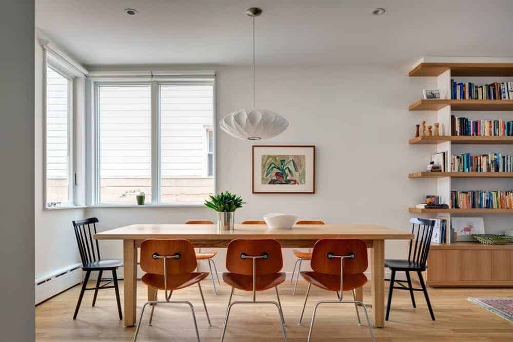 The white dining room offers black and amber chairs along with a light wood dining table illuminated by a white pendant light. It includes a bookshelf and a framed artwork mounted next to the glazed window.