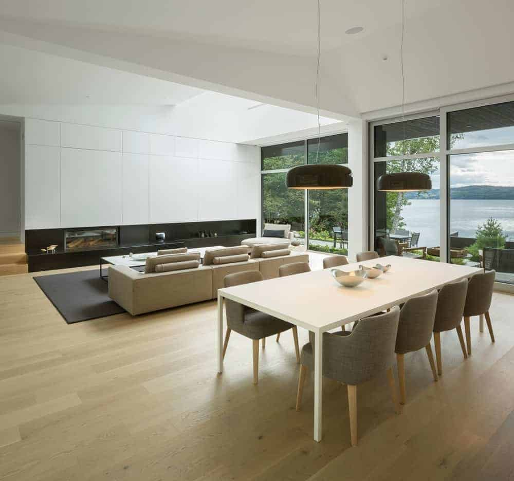 An open dining area with light hardwood flooring and full height windows overlooking the outdoor scenery. It includes black pendant lights and gray upholstered chairs along with a white dining table topped with decorative bowls.