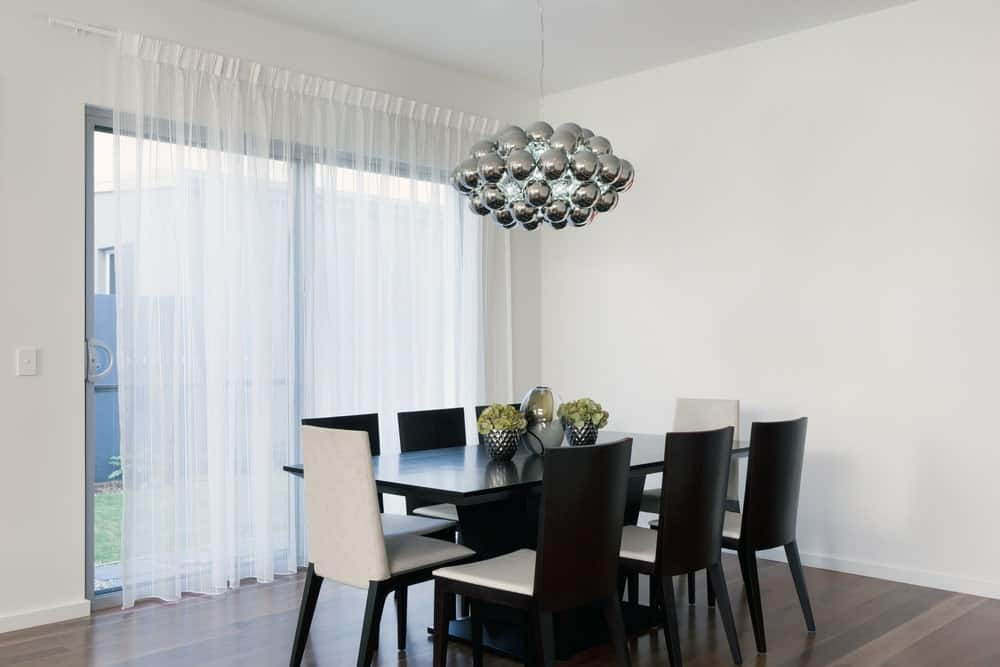 A cluster ball chandelier illuminates the black dining table that's topped with lovely vases. It is surrounded by white cushioned chairs over the hardwood flooring.