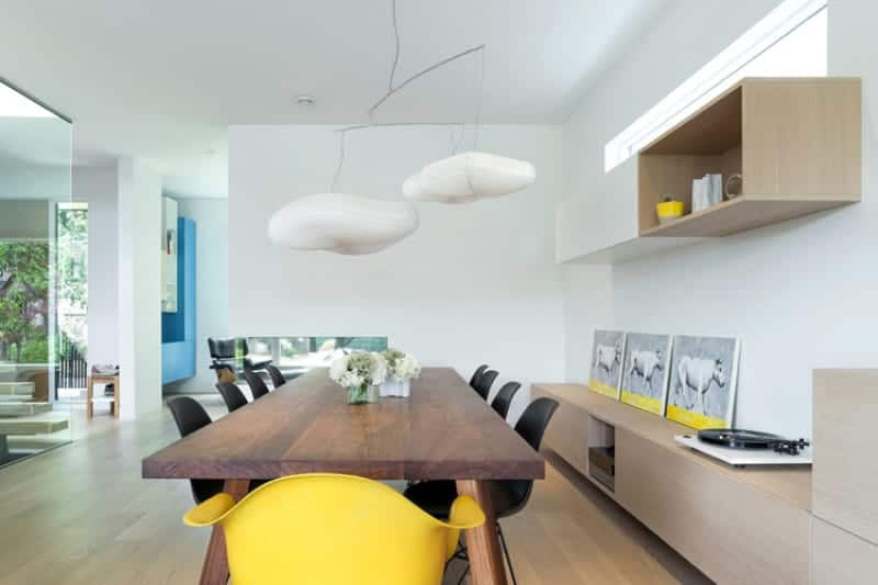 White dining room with subtle yellow accents from the animal wall arts and side chairs. It has floating cabinets and a modern dining set illuminated by unique pendant lights.