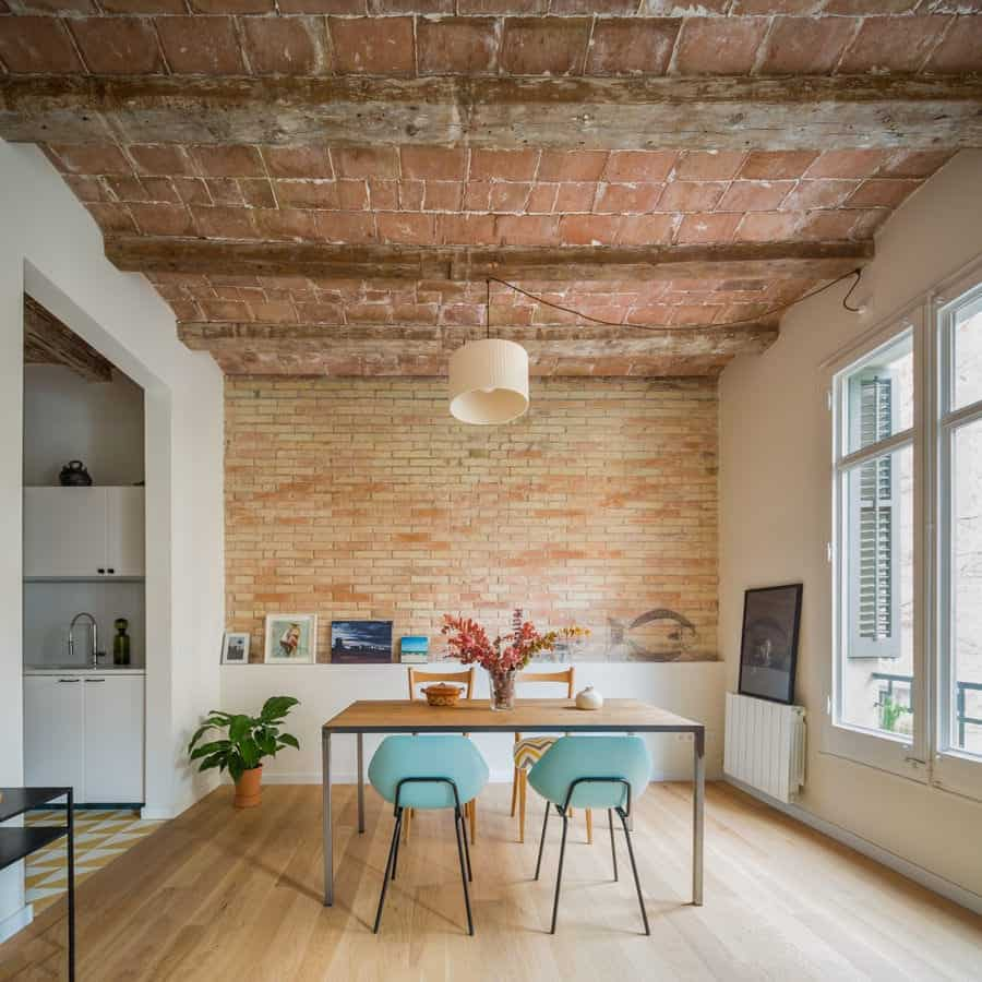 The contemporary dining room incorporated with a rustic style showcasing a brick accent wall and ceiling lined with exposed wood beams. It includes a drum pendant light and wood top dining table paired with mismatched chairs.