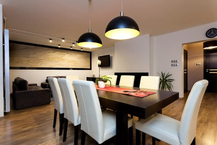 A pair of black dome pendant lights illuminate the dark wood dining table that's lined with a red runner. It is surrounded by white high back chairs over wide plank flooring.