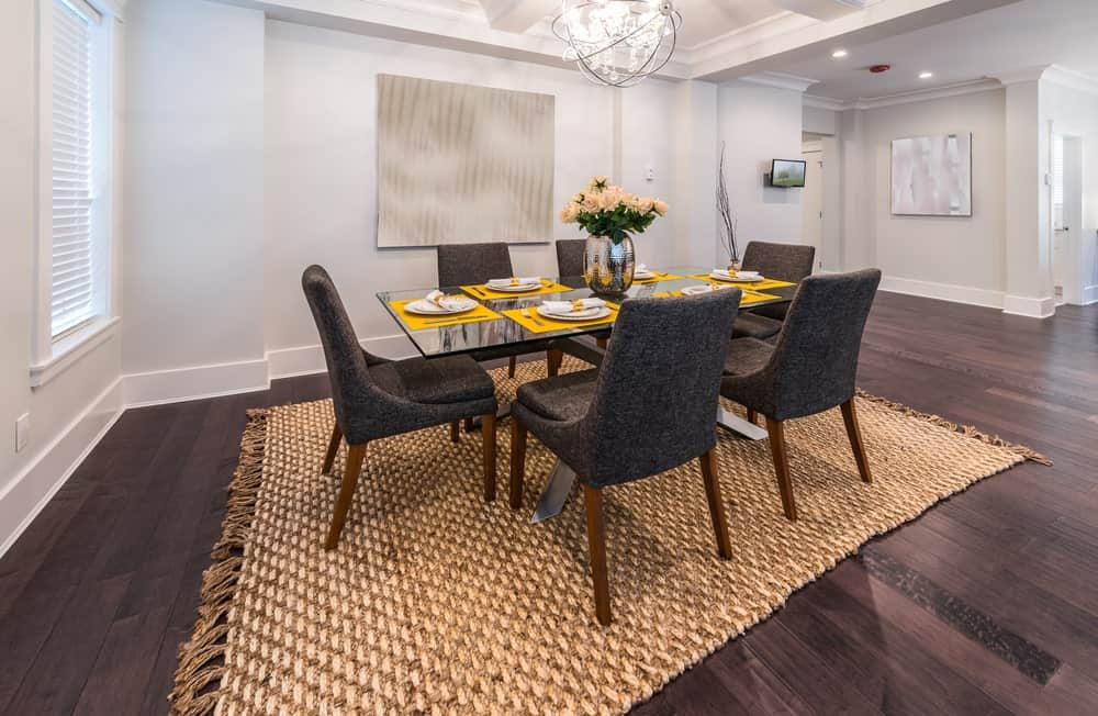 Dark wide plank flooring creates a sleek contrast to the white walls mounted with a large painting. This room boasts a glass top dining table and gray upholstered chairs over a knitted rug illuminated by a spherical pendant light.