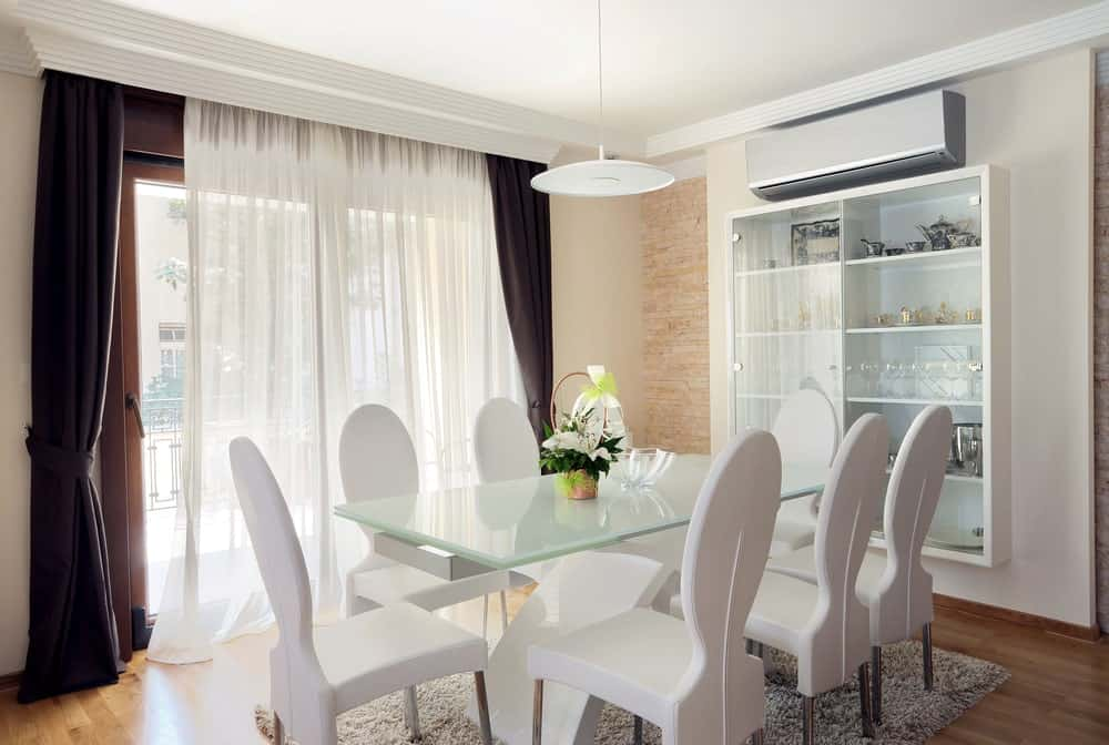 White round back chairs on a shaggy area rug surround a frosted glass top dining table illuminated by a sleek pendant light. It is accompanied by a wall mount display cabinet along with full height windows dressed in brown and sheer curtains.