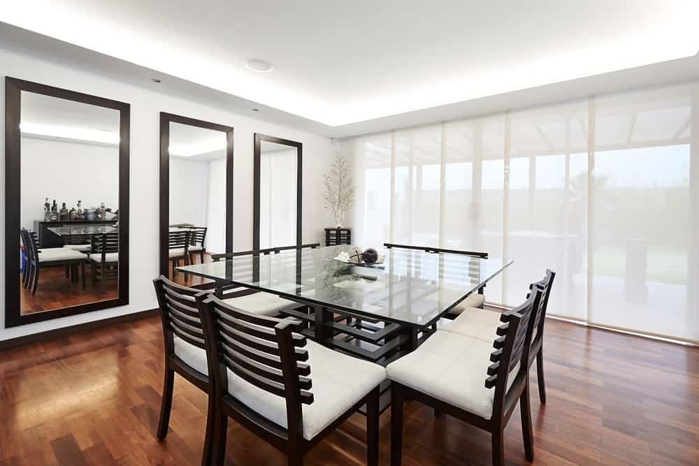 White dining room with glass top dining table and cushioned chairs complementing with the plant pedestal situated in the corner. It includes three full-length mirrors that create a larger visual space in the room.