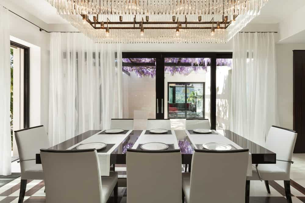 A fancy crystal chandelier hangs over the black high gloss dining table contrasted by white leather chairs. It is surrounded by white walls and full height glazing covered in flowy sheer curtains.
