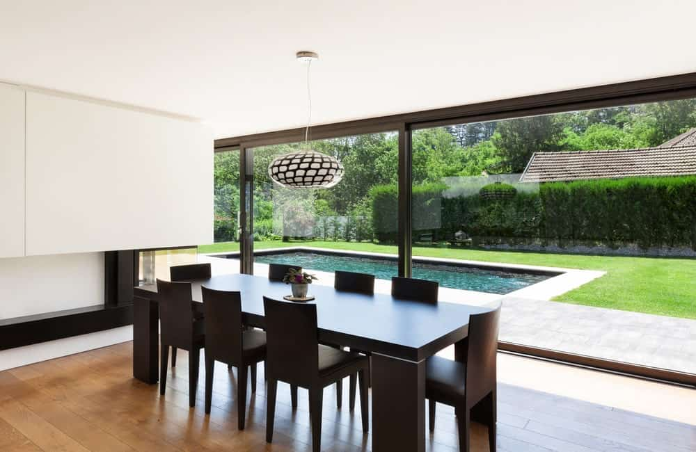 This dining room offers brown cushioned chairs and a matching rectangular dining table lighted by a round pendant light. It has wide plank flooring and panoramic windows overlooking the lush green yard with a serene pool.