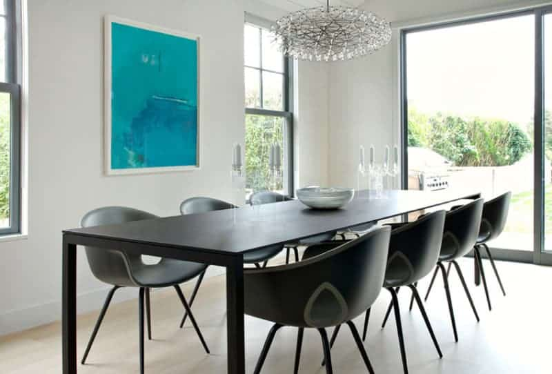Lovely blue wall art adds a pop of color in this dining room with round back chairs and a metal dining table under a round crystal chandelier. It has light hardwood flooring and glazed windows bringing plenty of natural light in.