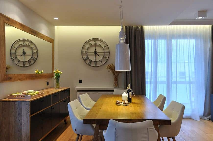 Warm dining room designed with a round wall clock along with a rectangular mirror that hung above the dark wood buffet table. It has a white pendant light and tufted chairs surrounding a wooden dining table that blends in with the hardwood flooring.