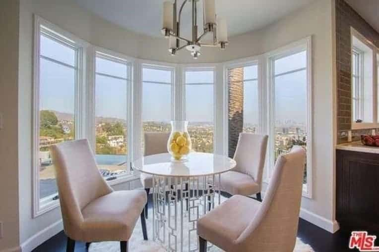 A small dining space situated by the glass paneled windows overlooking an expansive view. It has beige upholstered chairs and a stylish round dining table over a white faux fur rug lighted by a modern chandelier.