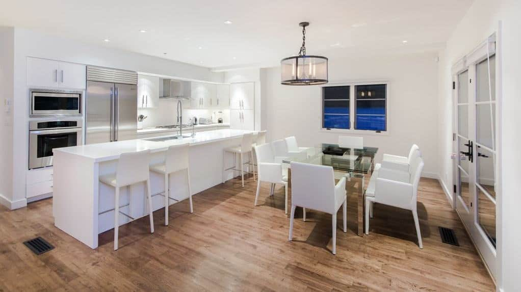 A dining area next to the kitchen featuring a glass top dining table and white modern chairs over the natural hardwood flooring. It is lighted by a drum chandelier along with recessed ceiling lights.