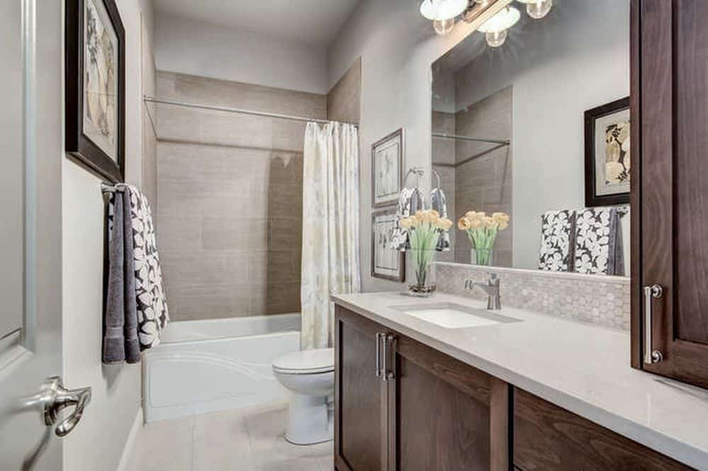 This bathroom is small but is infinitely cozy. The eggshell colored tiles pair so well with the wooden cupboards. The tasteful addition of flowers and a painting make it look even more inviting.