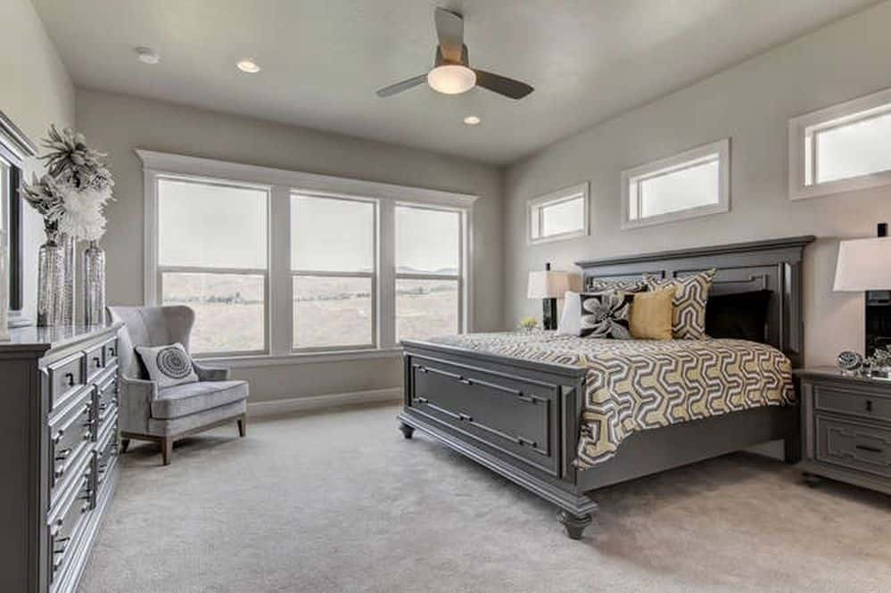 The neutral colors in this room create a calm atmosphere. Carpeted and shaded in gray, the room was completed with a queen size bed, single couch, storage cabinet, side lamps and double-hung windows.