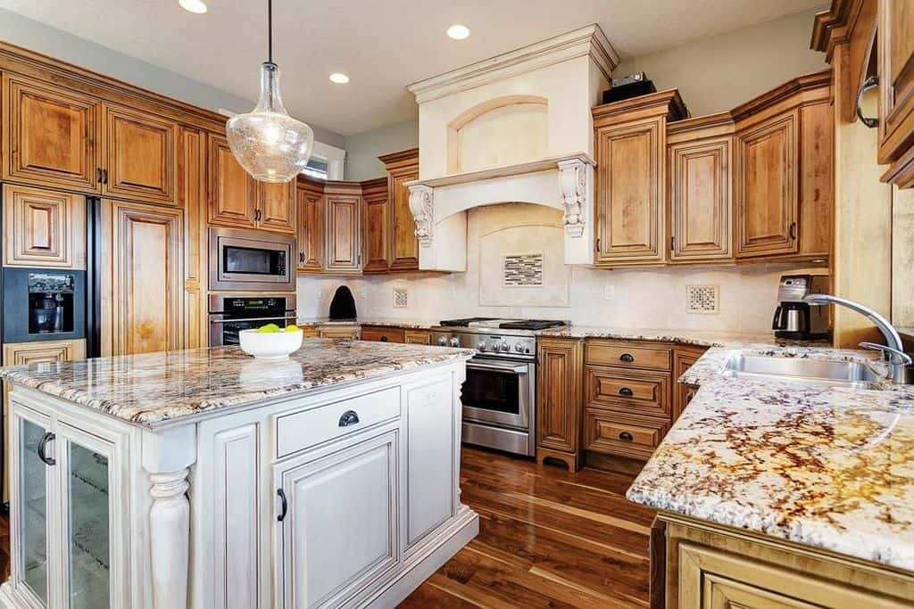 Gorgeous kitchen with white breakfast island, wood cabinetry, marble countertops, and hardwood flooring creates a beautiful, unified look.