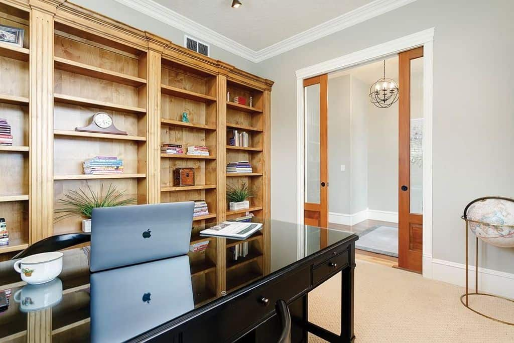 Modern home office with built-in shelving, gray walls and carpet flooring.